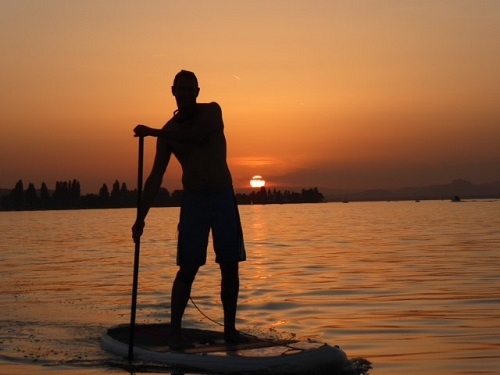 La Canoa Geschaeftsführer Kai König beim Stand Up Paddling im Sonnenuntergang auf dem Bodensee